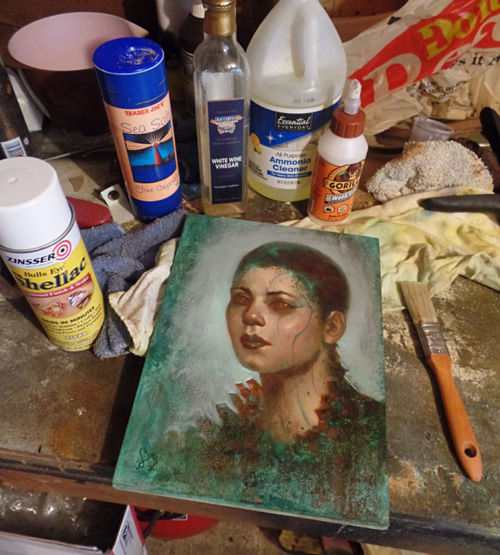 An oil painting by Jim Pavelec surrounded by the tools used to create the verdigris surface.